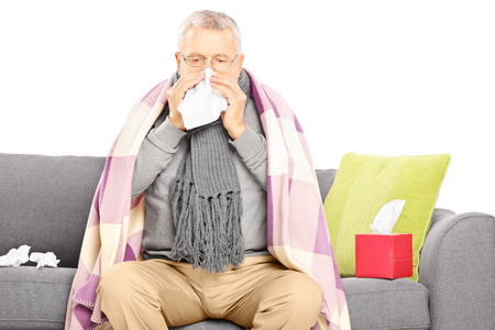 Sick senior man covered with blanket sitting on a sofa and blowing his nose isolated on white background
