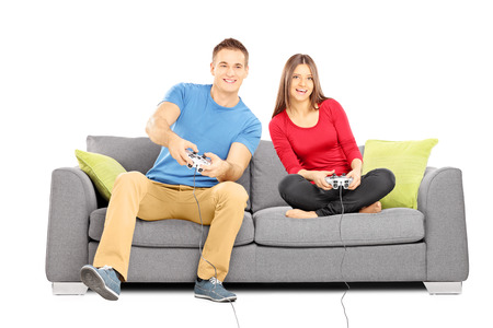 Young couple sitting on a modern couch and playing video games isolated on white background Stock Photo - 24159927