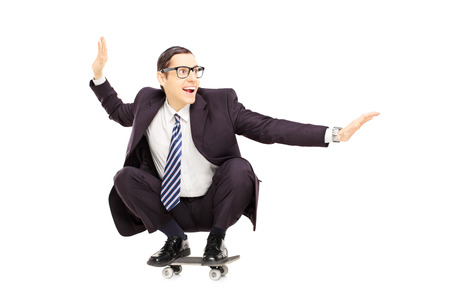 Young smiling businessman riding a skateboard isolated on a white background photo