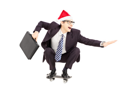 Young smiling businessman with briefcase and santa hat riding a skateboard isolated on a white background photo