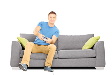 video games: Young smiling man seated on a sofa playing video games isolated on white background Stock Photo