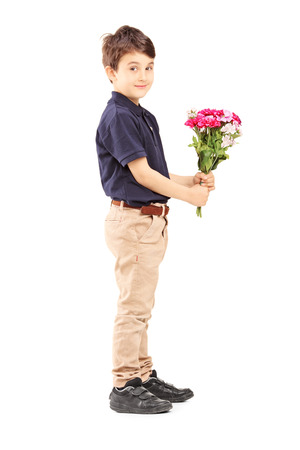 Full length portrait of a cute little boy holding bunch of flowers, isolated on white background photo