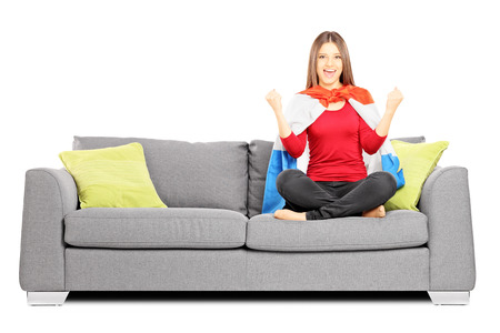 supporter: Young female sport supporter sitting on a modern sofa and cheering, isolated on white background