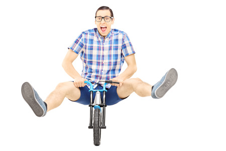 Crazy young man posing on a small bicycle isolated on white background photo