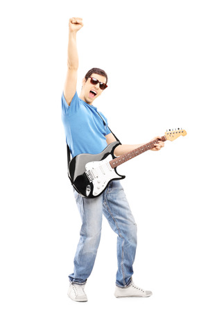 perform: Full length portrait of a happy guy playing on an electric guitar isolated on white background