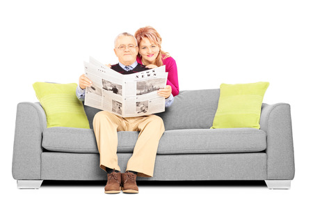 Middle aged couple with newspaper sitting on a sofa isolated on white background Stock Photo - 24390573