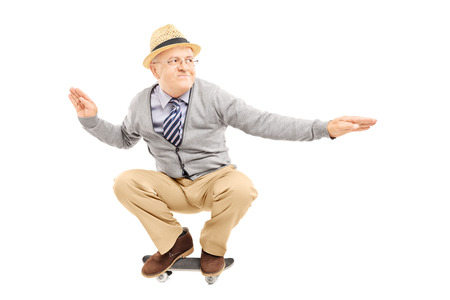 trasloco: Uomo anziano con il cappello in sella a una skateboard isolato su uno sfondo bianco Archivio Fotografico