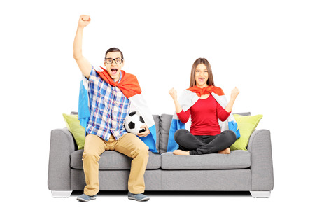 Young football supporters sitting on a modern sofa, isolated on white background photo
