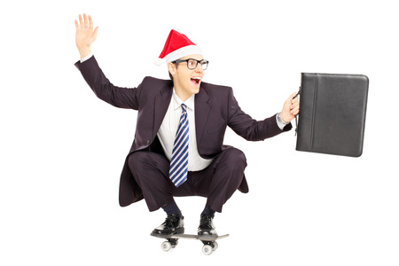 Young smiling businessperson with briefcase and santa hat on a skateboard isolated on a white background photo