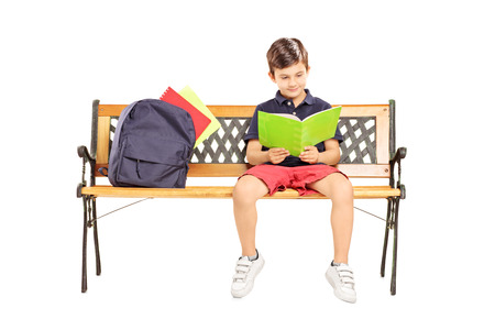 Schoolboy seated on a wooden bench reading a book isolated on white background photo