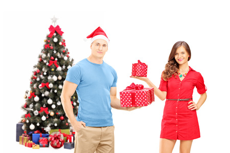 Smiling couple holding gifts and posing in front of a christmas tree, isolated on white background photo