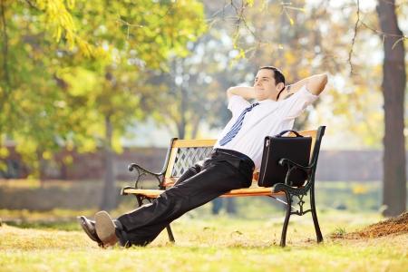 relajado: Empresario joven sentado en un banco de madera y de relax en un parque