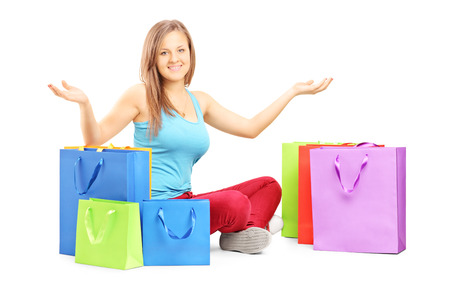 Young smiling woman sitting on a floor with many shopping bags and gesturing isolated on white background photo
