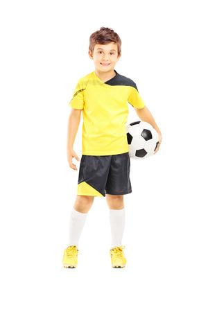 Volledige lengte portret van een jongen in sportkleding met een voetbal op een witte achtergrond