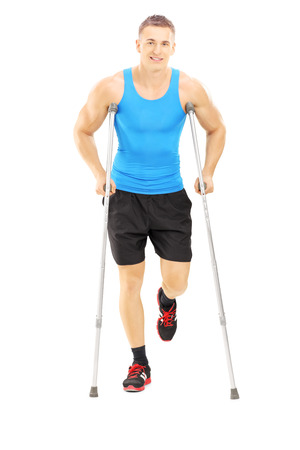 Full length portrait of an injured male athlete with crutches isolated on white background photo