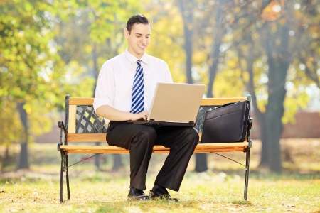 Businessman sitting on a wooden bench and working on a laptop in a park photo