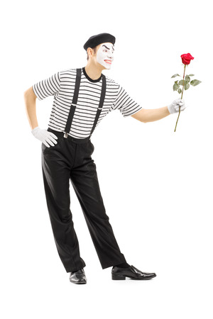 Full length portrait of a male mime artist giving a rose flower isolated on white background photo