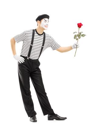 pantomima: Retrato de cuerpo entero de un mimo macho da una flor rosa aislada en el fondo blanco