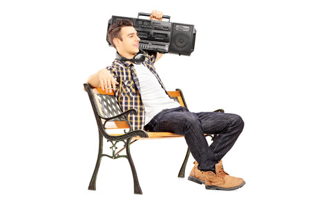 boombox: Guy holding a boombox on his shoulder and sitting on a wooden bench isolated on white background Stock Photo