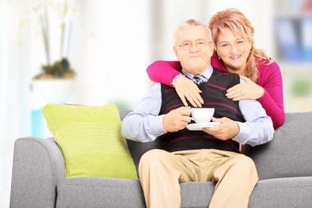 Middle aged couple posing during a coffee break at home photo