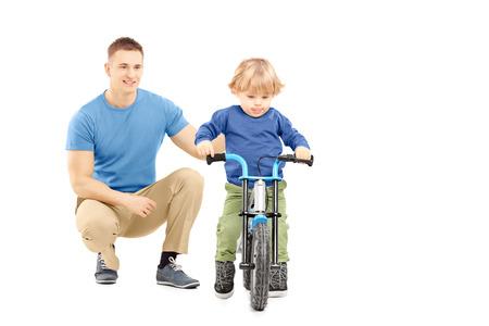 niños en bicicleta: Padre junto a su hijo tratando de montar una bicicleta aisladas sobre fondo blanco Foto de archivo