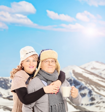 Mature smiling couple holding a cup and posing outside in snowy landscape, shot with a tilt and shift photo