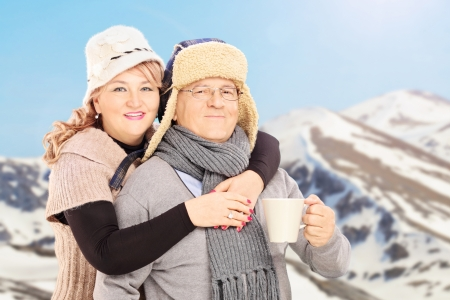 Mature smiling couple holding a cup and posing outside in snowy landscape photo