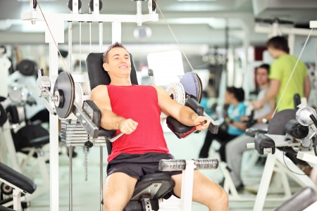 Smiling muscular young man exercising in a fitness club photo