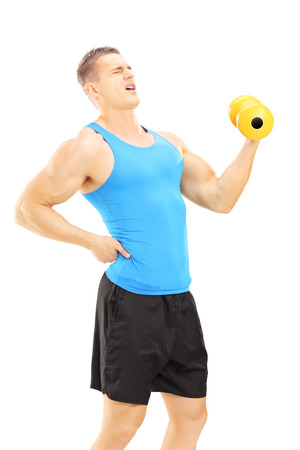 back injury: Young guy with back pain while lifting a dumbbell isolated on white background Stock Photo