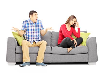 pareja discutiendo: Pareja heterosexual joven que se sienta en un sofá durante una discusión aislada en el fondo blanco Foto de archivo