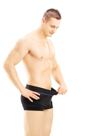 Young shirtless man looking in his pants isolated on white background photo