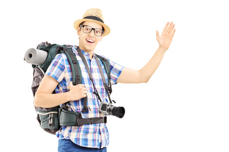 Male tourist with backpack waving with his hand isolated on white background photo