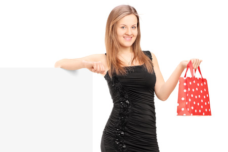 Young female with a gift bag standing next to a blank panel, isolated on white background photo