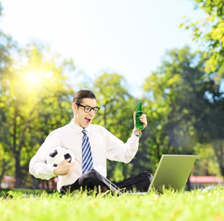 watching football: Cheerful man seated on a green grass watching football on a laptop in a park, shot with a tilt and shift lens