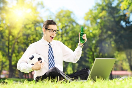 watching football: Cheerful man seated on a green grass watching football on a laptop in a park Stock Photo