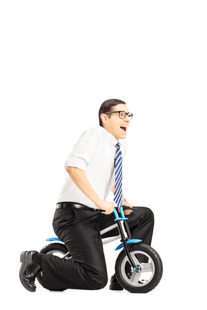 Excited young businessperson riding a small bicycle isolated against white photo