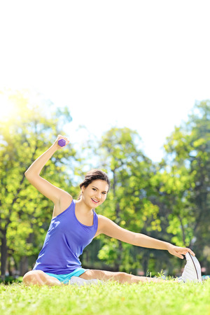 athletic wear: Young female athlete in sportswear in a park exercising with dumbbell  Stock Photo