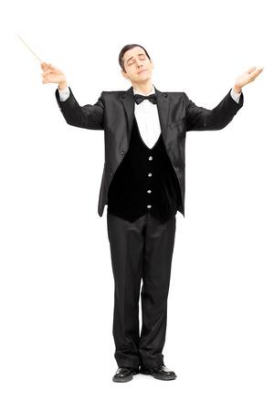 Volledige lengte portret van een mannelijke orkest dirigent regisseren met knuppel op wit wordt geïsoleerd