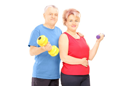 pilates man: Mature man and woman holding dumbbells and looking at camera isolated on white