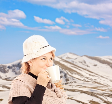 Mature smiling woman drinking a hot tea and posing outside in snowy landscape photo