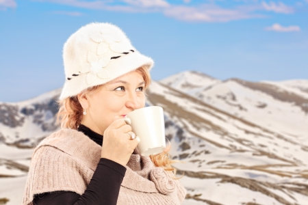 Mature smiling woman drinking a hot tea and posing outside, with snowy mountain photo
