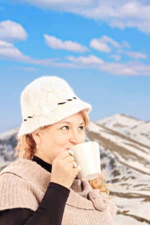 Mature smiling woman drinking a hot tea and posing, with snowy mountain photo