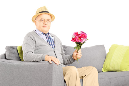 Senior gentleman sitting on a modern sofa and holding a bunch of flowers, isolated on white Stock Photo - 24436847