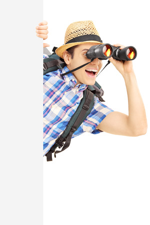 Smiling male tourist looking through binocular behind a blank panel isolated on white photo