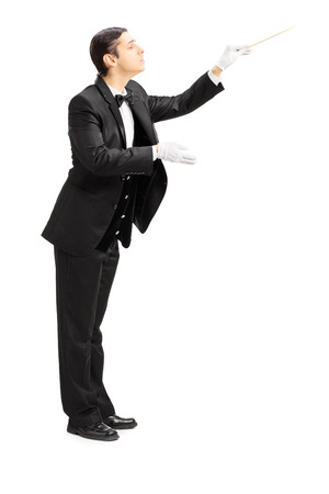 Full length portrait of a male orchestra conductor directing with stick isolated on white background photo