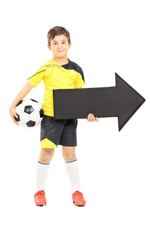 plimsoll: Full length portrait of a smiling boy in sportswear holding a soccer ball and black arrow pointing right isolated on white background Stock Photo