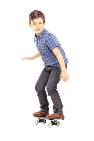 ni�o en patines: Retrato de cuerpo entero de un joven lindo que monta un pat�n aislados sobre fondo blanco