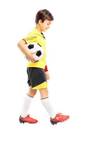 スポーツウェアの白い背景で隔離のサッカー ボールと一緒にポーズ悲しい子供の完全な長さの肖像画
