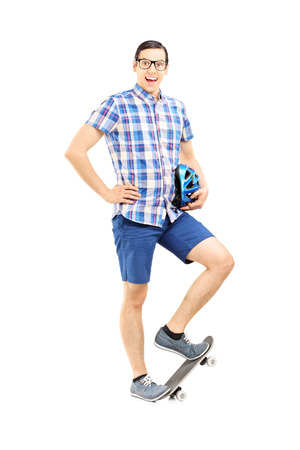skate board: Full length portrait of a smiling guy holding a helmet and standing on a skate board isolated on white background Stock Photo