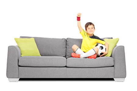 Happy boy in sportswear with a soccer ball sitting on a sofa and gesturing happiness isolated on white background Stock Photo - 24460132